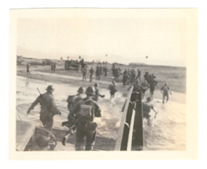 Soldiers running off a boat onto the beach.