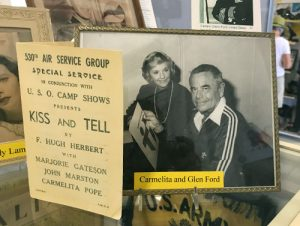 Warhawk Air Museum display including image of Carmelita Pope and Glen Ford and a program for the play 'Kiss and Tell'