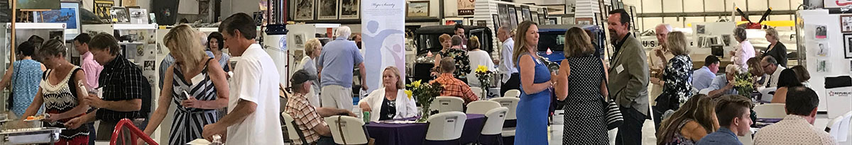 People mingling at a corporate event hosted at the Warhawk Air Museum