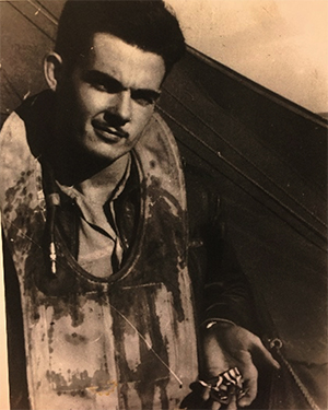John Hoye, covered in his own blood, holding two medals.