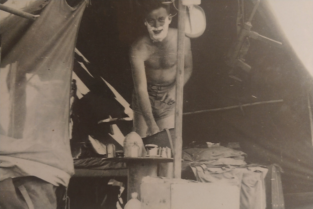 David shaving in a tent.